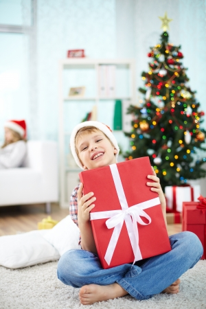 Portrait of cheerful boy with big red giftbox looking at camera on Christmas evening photo