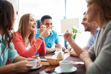 riendo: Retrato de amigos adolescentes felices sentados y charlando en la cafeter�a