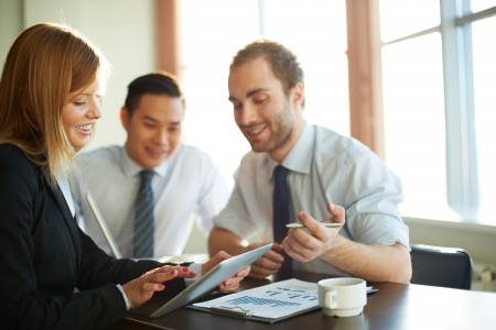 group strategy: Portrait of smart businesswoman showing her partners something in touchpad at meeting Stock Photo