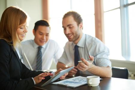 la gente de trabajo: Retrato de mujer de negocios inteligente, mostrando a sus compa�eros algo en touchpad en la reuni�n Foto de archivo