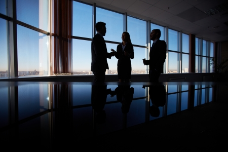 Outlines of three office workers interacting by the window Stock Photo