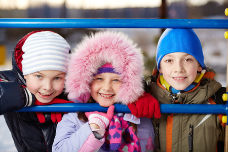Happy kids in winterwear looking at camera outside photo