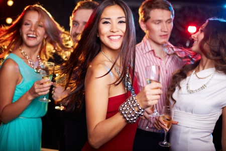 dancing disco: Portrait of cheerful girl with champagne flute dancing at party while smiling at camera