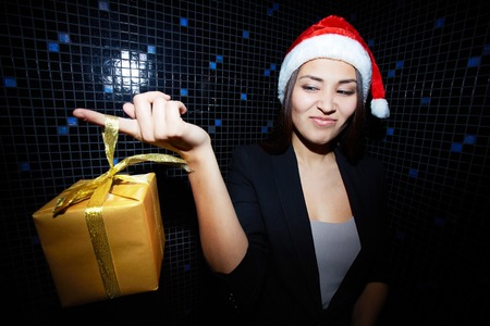 sneer: Portrait of young businesswoman in Santa cap holding Chistmas gift and looking at it with sneer