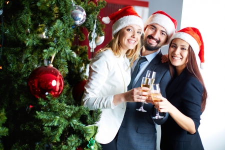 Portrait of joyful colleagues in Santa caps toasting with champagne by Christmas tree  Stock Photo