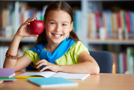 Portrait of happy schoolgirl with big red apple looking at camera in library photo