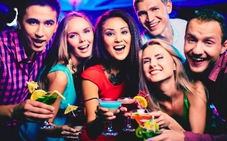 Grupo de amigos felices con los cócteles que tuesta en el partido