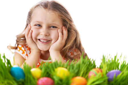 Happy girl looking at camera while lying in green grass with colorful Easter eggs in it