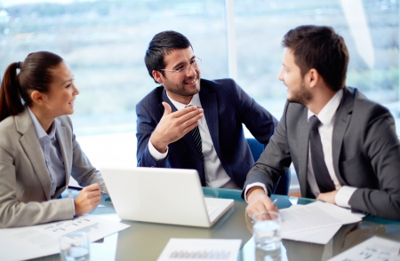 Portrait of three co-workers discussing business plan in office