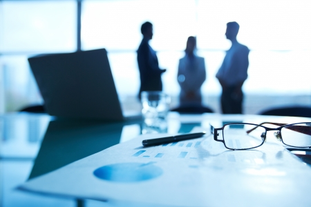 unrecognized: Close-up of business document, pen and eyeglasses at workplace on background of office workers interacting Stock Photo