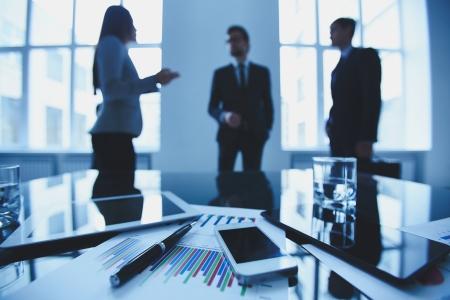 reuniones empresariales: Primer plano de objetos de negocio en lugar de trabajo en el fondo de los trabajadores de oficina que interact�an Foto de archivo