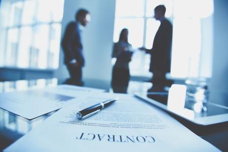 contratos: Close-up del contrato de negocios con la pluma en el lugar de trabajo en el fondo de los trabajadores de oficina que interactúan Foto de archivo