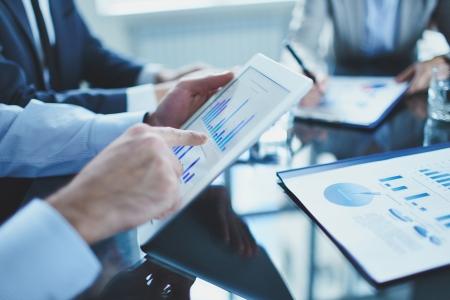 Afbeelding van ondernemer wijzend op document touchpad op vergadering