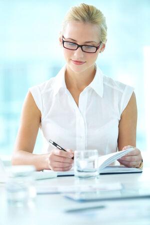 Portrait of pretty businesswoman making notes photo