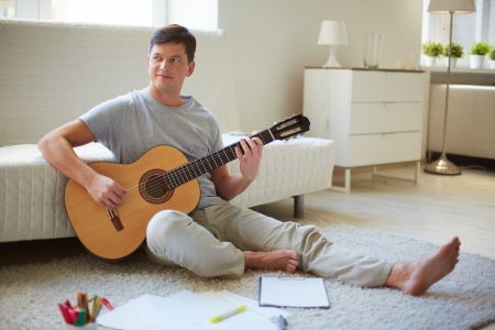 Portrait of handsome young man holding guitar and playing it photo