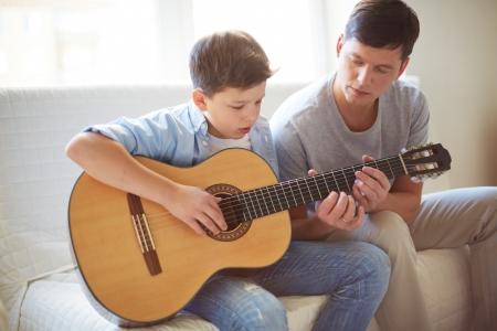 hombre sentado: Retrato de hombre joven y guapo enseñando a su hijo a tocar la guitarra