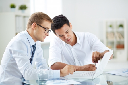 trabajando: Retrato de hombres de negocios inteligentes discuten proyecto en el portátil en la reunión