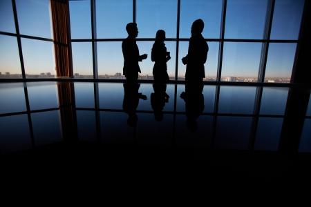 Outlines of group of white collar workers interacting by the window in office photo