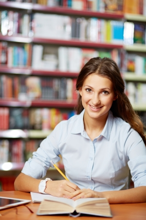 Portrait of pretty student looking at camera while working in college library Stock Photo