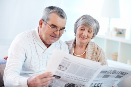 reading news: Portrait of happy mature couple sitting at home and reading newspaper together