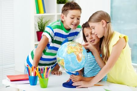 niños estudiando: Retrato de compañeros felices en el lugar de trabajo que estudia el globo en el aula