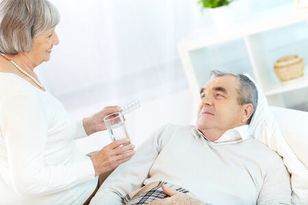 Portrait of mature woman giving tablets and glass of water to her sick husband at home Stock Photo - 24984556