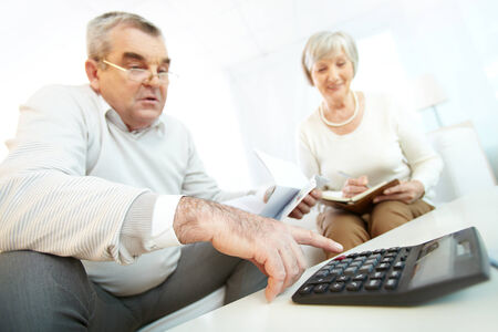 Mature man and his wife making financial revision at home photo