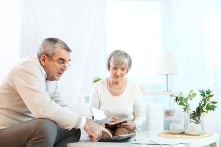 planificación familiar: Retrato de hombre maduro y su esposa haciendo la revisión financiera en el hogar