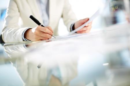 documentos: Manos de la empresaria joven firma de papel