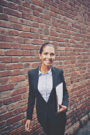 Image of happy businesswoman with document walking along brick wall photo