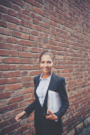 Image of happy businesswoman with document walking along brick wall and looking at camera