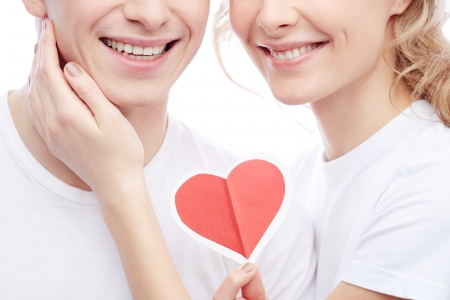 Close-up of amorous young girl holding red heart and touching her boyfriend