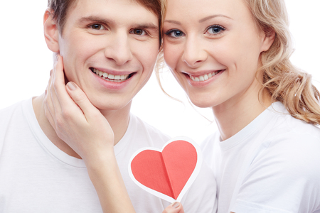 young couple smiling: Portrait of amorous young girl holding red heart and touching her boyfriend Stock Photo