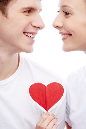 Portrait of a young beautiful couple smiling at each other while girl holding red paper heart Stock Photo - 24984675
