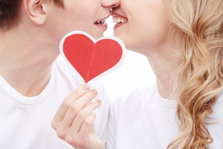 Close-up of young amorous couple touching by their faces while girl holding red paper heart