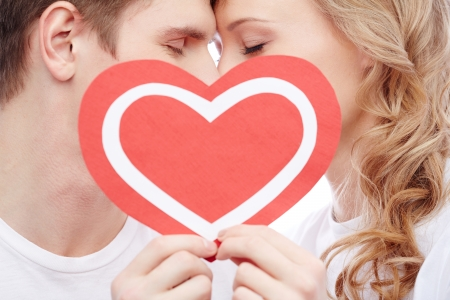 Two young dates behind paper heart with their faces close to one another Stock Photo