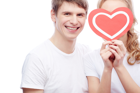 Portrait of happy guy looking at camera with his girlfriend near by holding red heart by her face photo