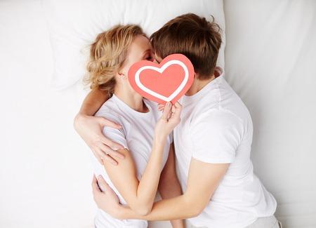 enamorados en la cama: Dos fechas jóvenes detrás de corazón de papel con su cara cerca de uno al otro