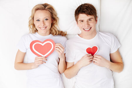 inlove: Portrait of happy guy and his girlfriend holding red hearts by their chest and looking at camera