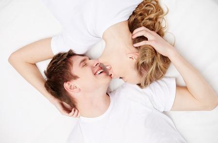 couple au lit: Deux jeunes dates heureux avec les yeux ferm�s allong� dans son lit et de rire Banque d'images