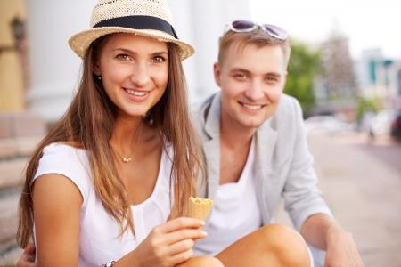 hanging around: Muchacha feliz y su novio mirando la c�mara mientras merodeando fuera Foto de archivo