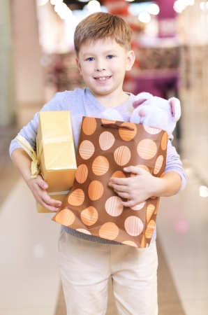 Portrait of happy child holding paperbag with teddy bear and giftbox photo