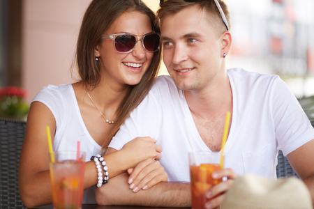 Young guy and his girlfriend sitting in cafe on summer day Stock Photo - 24984889