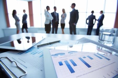 företag: Närbild av affärsdokument i pekplattan som ligger på skrivbordet, kontorsarbetare interagerar i bakgrunden