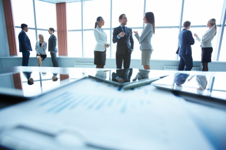 success focus: Business people interacting in office with workplace in front of them