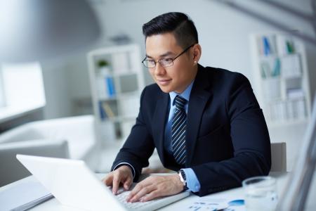 オフィスでラップトップに入力するスーツのビジネスマンを笑顔 写真素材