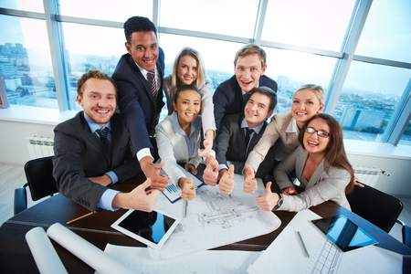 competent: Group of business partners sitting at workplace in office and showing thumbs up Stock Photo