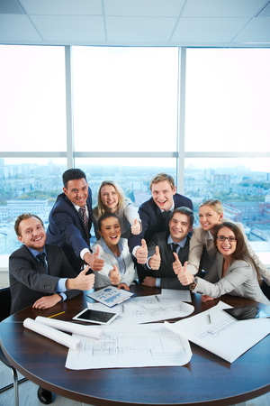 competency: Group of business partners sitting at workplace in office and showing thumbs up Stock Photo