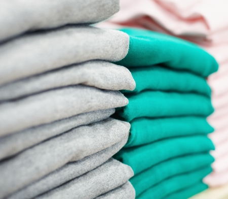 pullovers: Stack of new green and grey pullovers in clothing department