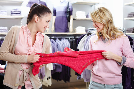 disinclination: Image of two greedy girls fighting for red tanktop in department store Stock Photo